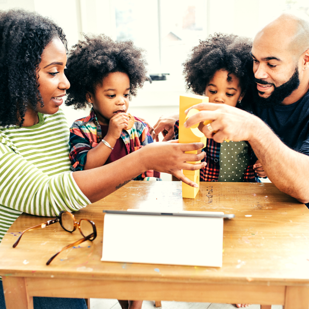 Lead by example when teaching your kids about money. Parents building blocks with kids.