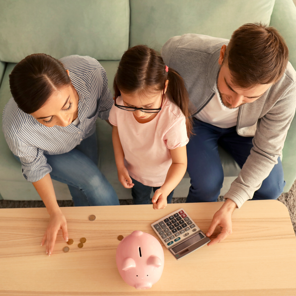 Encourage kids to budget and save. Parents helping daughter count coins to put into piggy bank.